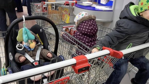 Drei Kinder im Einkaufswagen